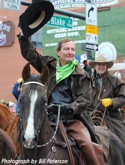 Joseph Murr on his horse waving his cowboy hat in the air riding in Downtown Denver during the St. P