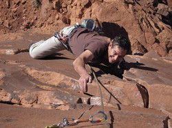 Rick Accomazzo climbs a vertical rock face and grimaces to reach his hold