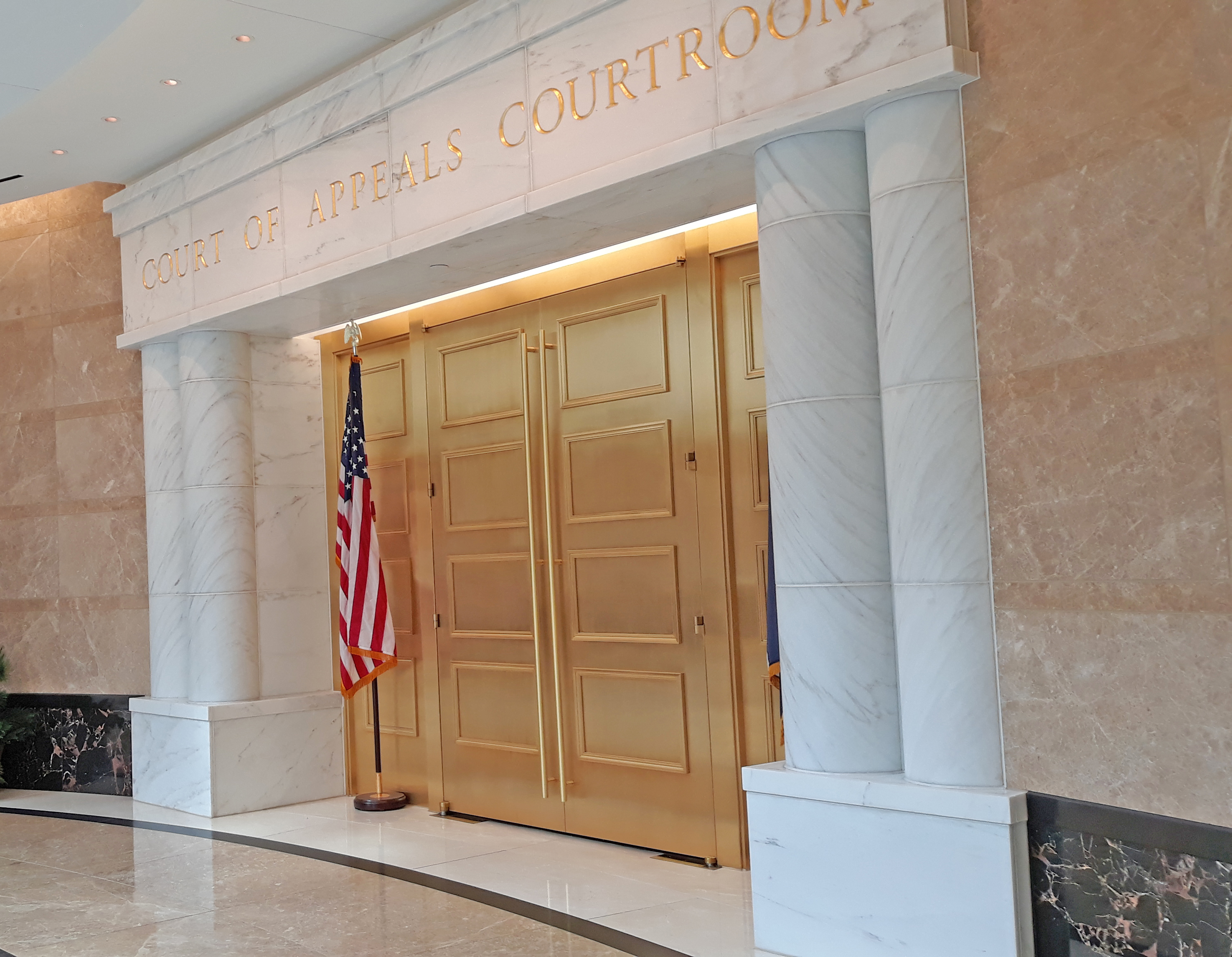 Double doors of a courtroom inside the Colorado Court of Appeals Courthouse with the American flag b