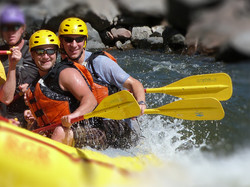 Firm members whitewater rafting on the Arkansas River in Colorado with paddles in hands, wearing lif
