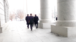 Firm attorneys walk outside along the pillars of the Colorado Supreme Court Courthouse