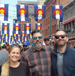 Firm members stand under flags of Colorado strung above Larimer square while attending the annual Fi
