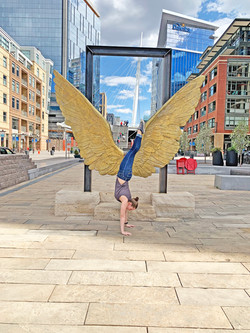 Staff member doing a hand stand in front of the Luz De Denver wings in Riverfront Park Lodo Denver C