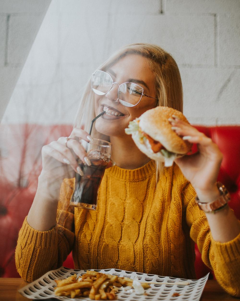 Teenager eating a high iron hamburger