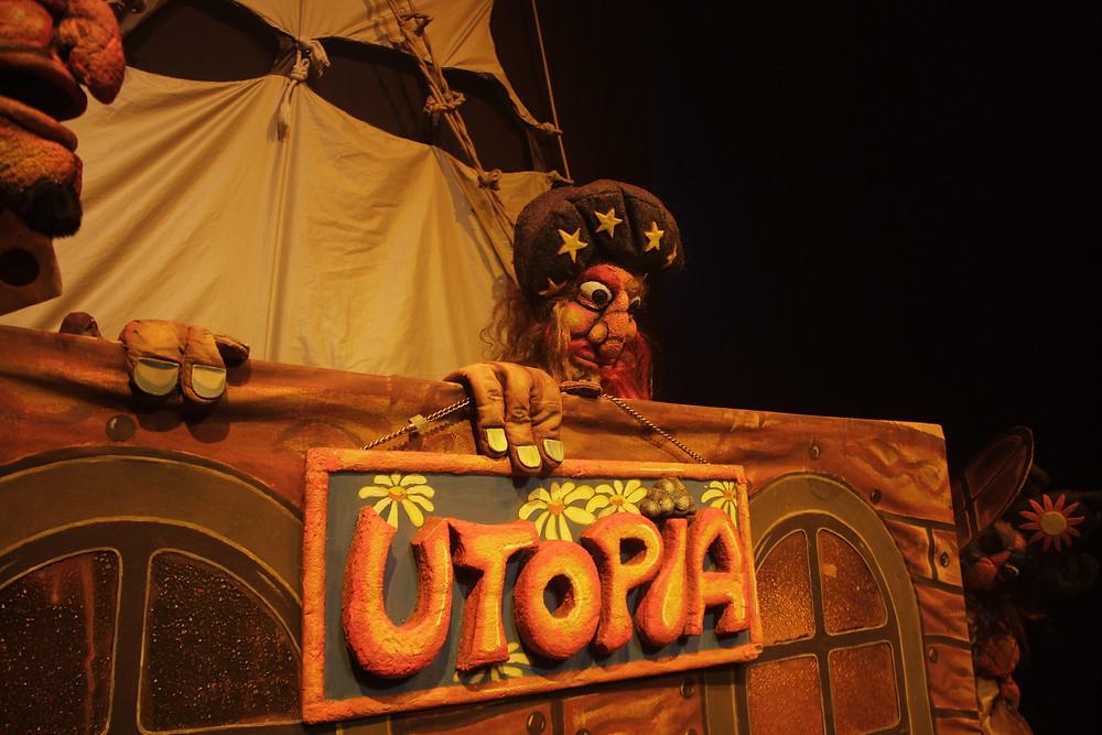Titere sostiene letrero que dice utopia