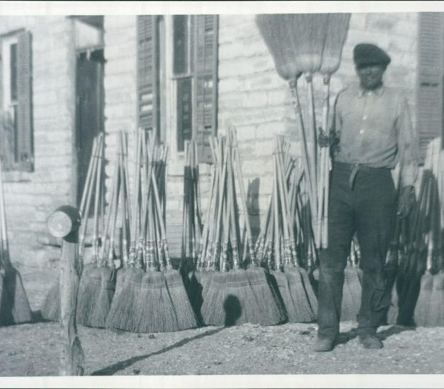 Great-Uncle Johnny Morris with brooms at the family home in Coolidge, Kansas