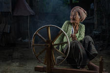 Old Balinese lady with her spinning wheel
