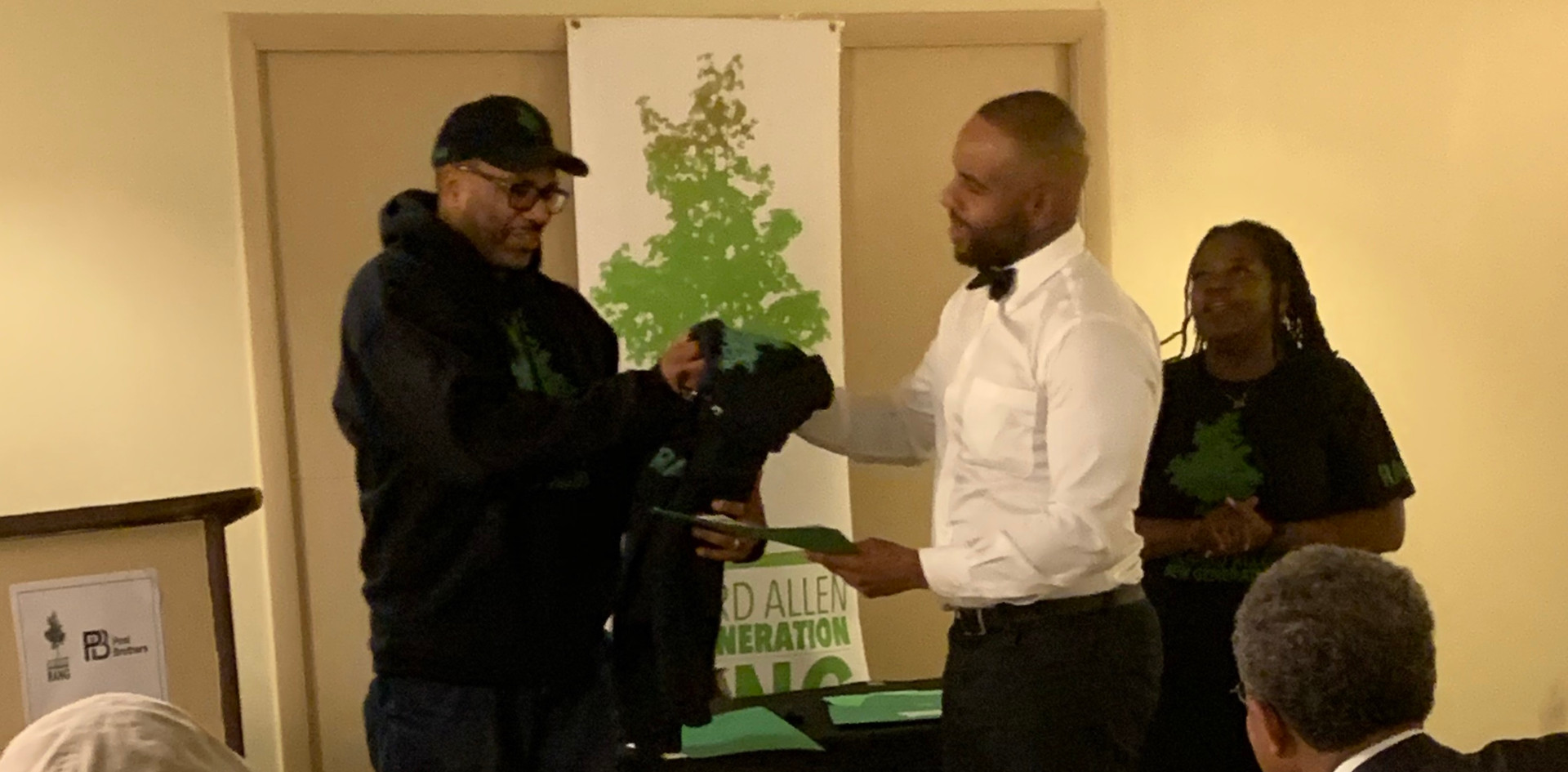 """At the recent Richard Allen New Generation(RANG) Pre-Apprentice Program's Graduate Recognition Dinner, held at the Gladys B. Jacobs Manor, at 1100 Fairmount Avenue, RANG President Bernard Gorham, (standing, left) presents a completion certificate and a """"First Class Of Graduates"""" RANG hoodie to pre-apprentice graduate, and new employed apprentice, Everette Burk."""