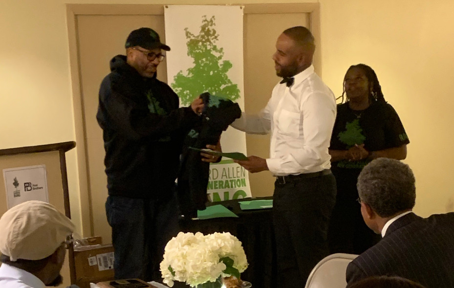 "At the recent Richard Allen New Generation(RANG) Pre-Apprentice Program's Graduate Recognition Dinner, held at the Gladys B. Jacobs Manor, at 1100 Fairmount Avenue, RANG President Bernard Gorham, (standing, left) presents a completion certificate and a ""First Class Of Graduates"" RANG hoodie to pre-apprentice graduate, and new employed apprentice, Everette Burk."