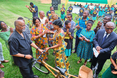 Chairman A. Bruce Crawley handing bamboo bicycle over to Deputy Minister Elizabeth Sackey to hand over to the children.