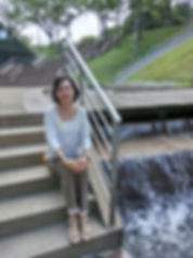 Me sitting on stone steps, right beside a ornamental waterfall.