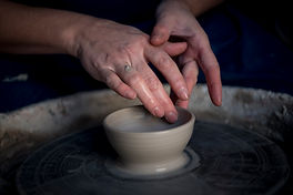 Handcrafting a small stoneware bowl on the potter's wheel.