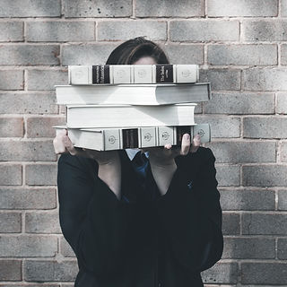 person%20holding%20pile%20of%20books%20n