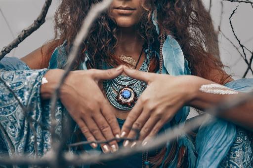 woman's hands blue necklace hippie dress