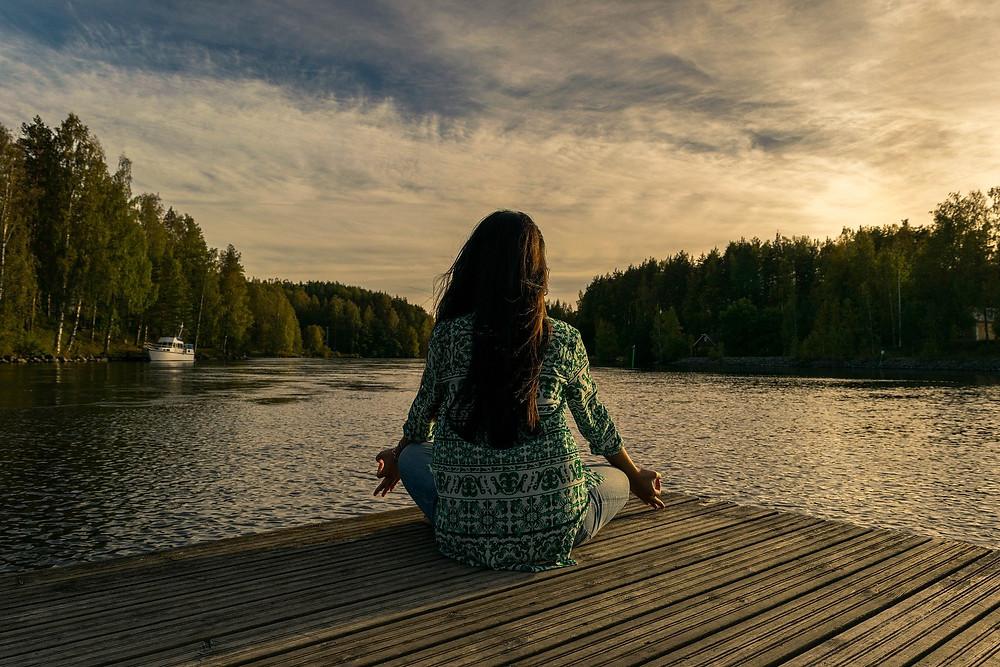 woman facing lake water meditating boat and background trees