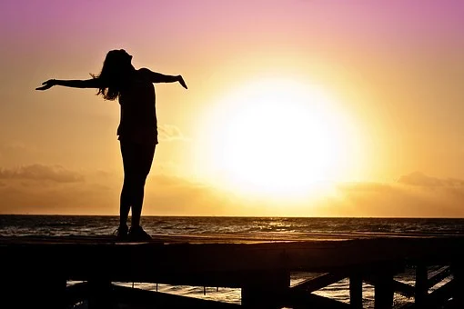 woman silhouette with arms outstretched towards the sun