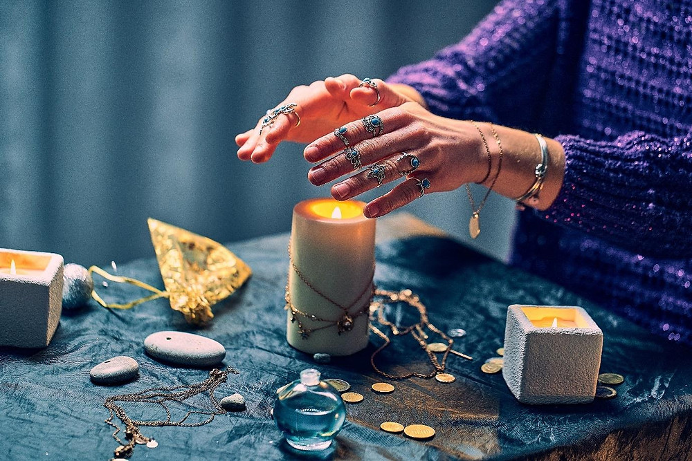 Candles and hands with rings and jewellery and coins