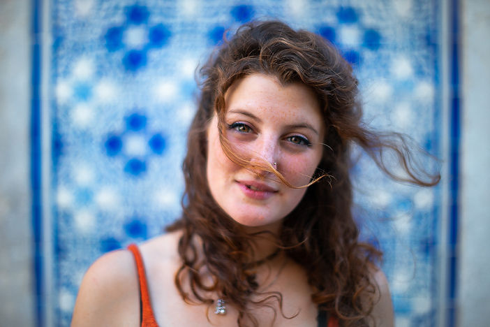 portrait of woman with green eyes and freckles looking into the camera. Her hair blowing in the wind as she stands in front of a blue tiled wall found in Lisbon, Portugal.