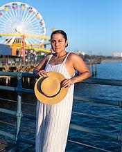 woman holding hat on Santa Monica pier.j
