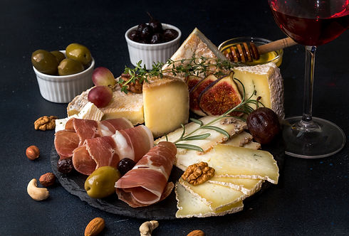 Glass of red wine and cheese plate with