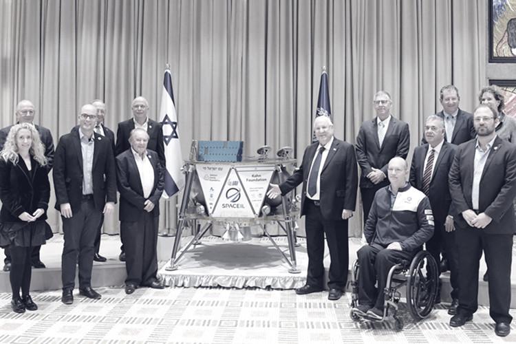 הנשיא ראובן רבלין יחד עם אנשים אחרים מציגים את חללית בראשית