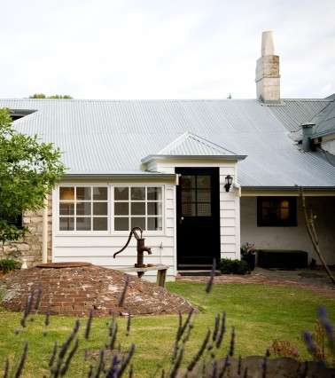 Taken from the back garden this photo shows the rear of the cottage and its back door.  Also in the photo is the well with its original hand pump - the bricks were ballast from an old sailing ship that sank out in the bay in the 1800s.
