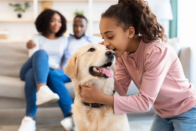 Portrait of smiling African American girl whispering something in the ear to her pet, tell