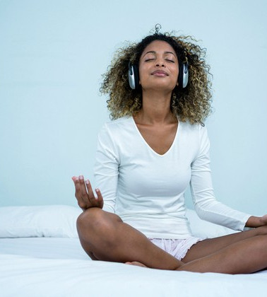 black-woman-meditating-on-bed-with-headp
