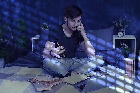 jovem-barbudo-concentrado-sentado-com-as-pernas-cruzadas-na-cama-e-estudando-on-line-usando-um-lapto