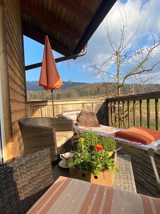 Sonnenbalkon mit Liegebett und Hängematte sowie Tisch und Sessel