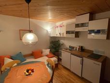 Küche mit Kaffeemaschine, kleinem Backrohr und Kühlschrank mit Gefrierfach