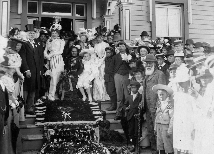 GP (standing) and Airini (seated) on the steps of Crissoge with the guests. The gentleman standing right with white beard and hat is Te Teira Tiakitai.