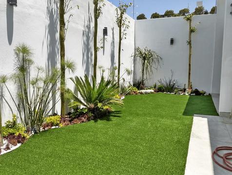 Jardineras rodeadas de pasto sintético