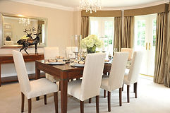 A luxurious dining room with table and c