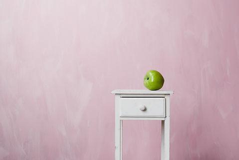 A green apple lies on a white pedestal o