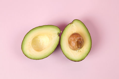 two avocado half with seed on a pink bac