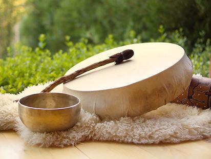 Tambour chamanique et bol tibétain pour sonothérapie, thérapie par les sons, les virations sonores, posés sur une peau de mouton dans la nature