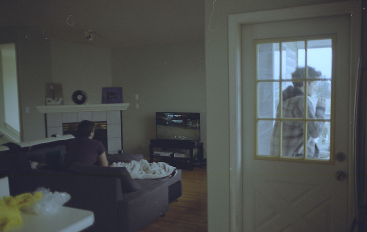Photograph. One person plays a video game in background. In foreground we see someone smoking a cigarette through the window of a door.