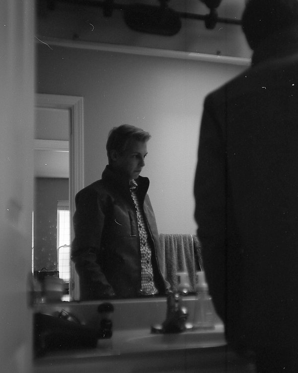 Black and white photo of a person standing in front of a mirror looking down to the right pensively.