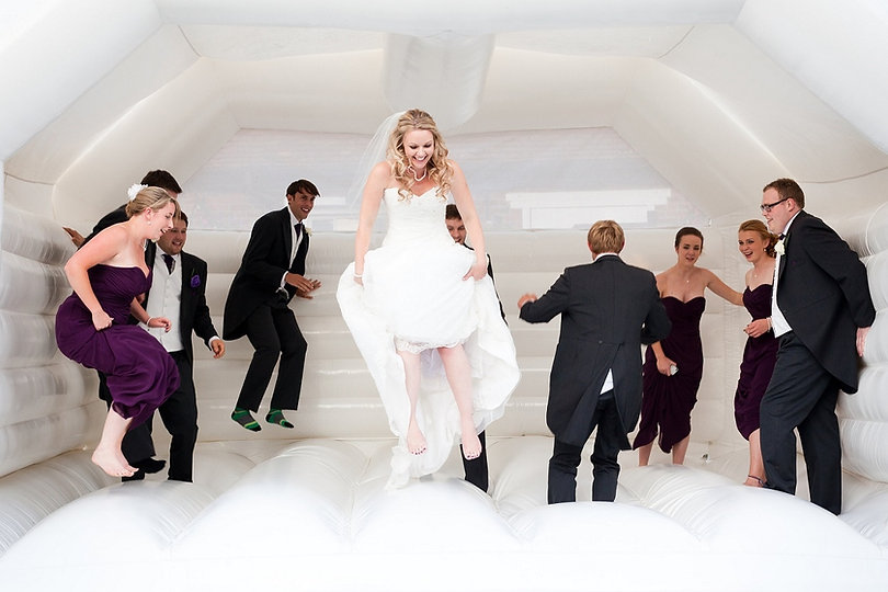 Bride and bridal party jumping in white bounce house atwedding