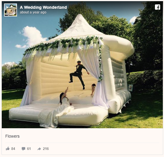 Bride, groom, and flower girl jumping in white wedding bounce house