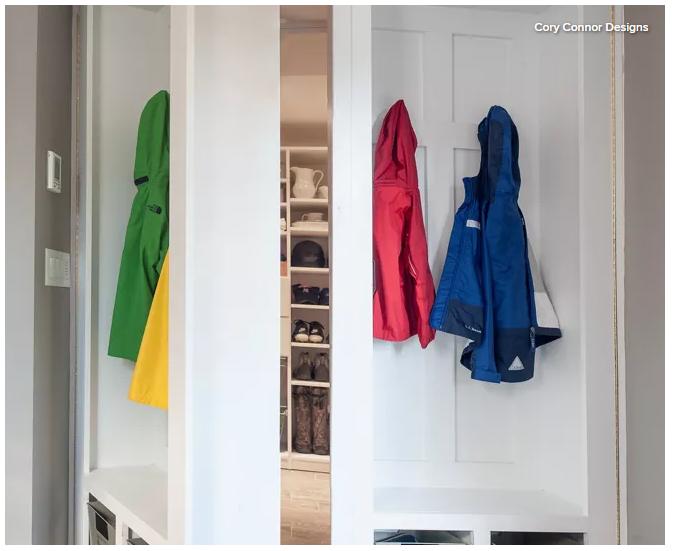 Hidden pantry storage behind built in white locker cabinets