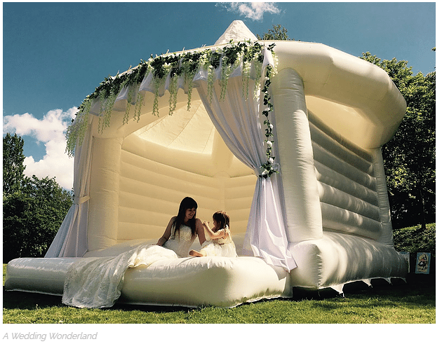 Bride and flower girl in white wedding bounce house