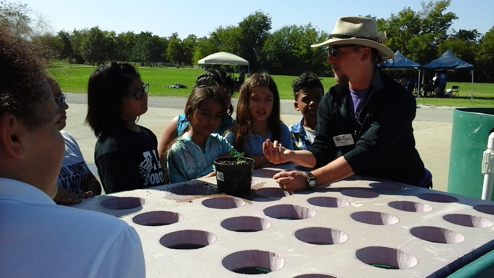 Discussing aquaponics at Farm to Market event with elementary students.