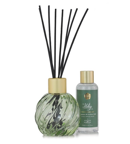 green glass diffuser vessel with sticks and a bottle