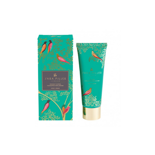 Green box with bird pattern next to a tube of hand cream