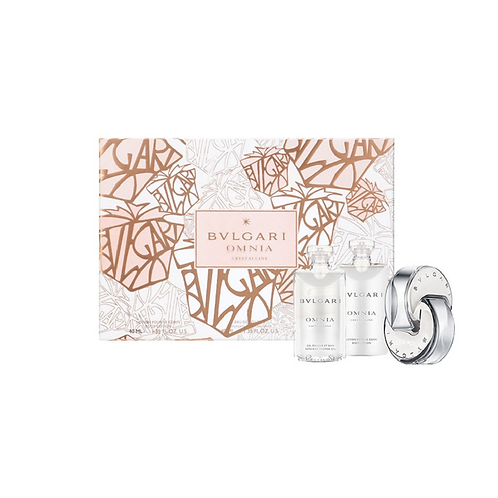 white, bronze and gold patterned box with perfume and hand cream in front