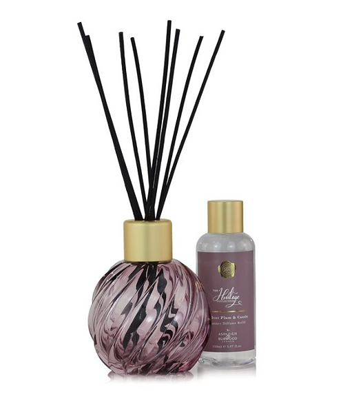 Pink glass diffuser vessel with sticks and a bottle