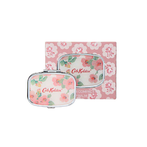 Mirror and lip balm compact with flowers in front of floral box