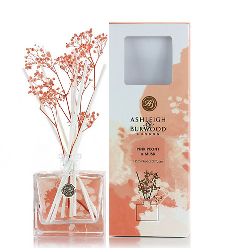 Clear glass bottle with floral reeds and orange and white box